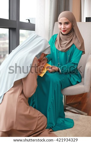 Young Beautiful Muslim Woman in head scarf with modern clothes asking forgiveness from elder sister during Hari Raya Aidilfitri - stock photo
