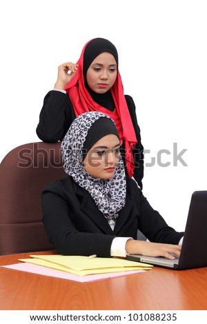 Young beautiful muslim women serious in business wear working in office together - stock photo