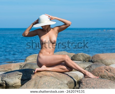 Young beautiful naked woman in white hat enjoying summer time on the beach - stock photo