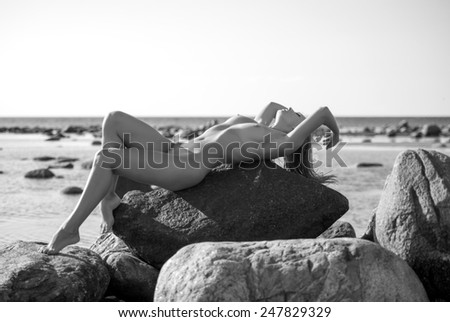 Young beautiful naked woman posing on stones near the sea. Enjoying summer time - stock photo