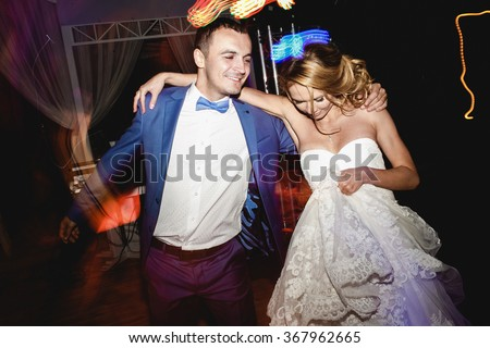 Young beautiful newlyweds dancing with the guests in night club or restaurant at her wedding evening - stock photo