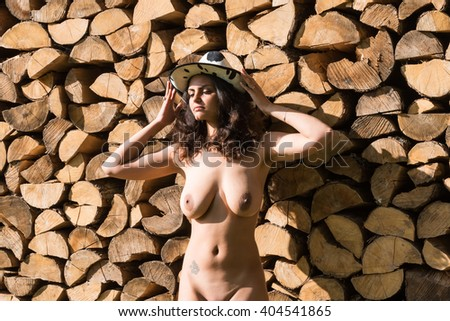 Young beautiful nude woman in hat posing against pile of wooden logs - stock photo