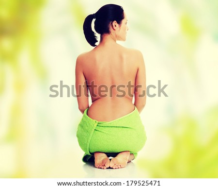 Young beautiful nude woman with towel - stock photo