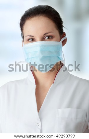 Young beautiful nurse in mask - stock photo