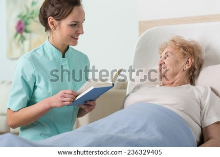 Young beautiful nurse reading to sick older woman in bed - stock photo