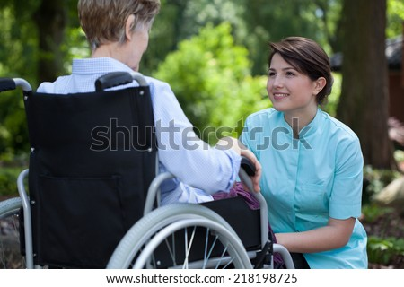 Young beautiful nurse spending sunny day with disabled woman at park - stock photo