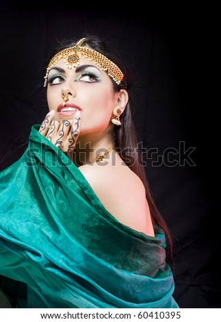 young beautiful oriental style woman covering herself with a green veil - stock photo