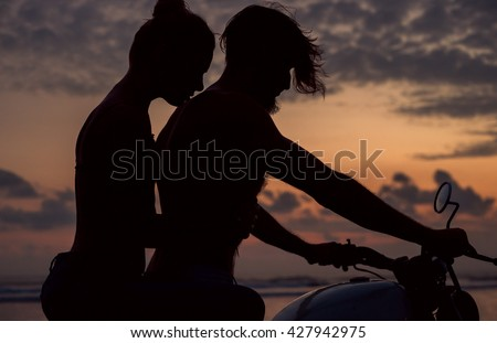 young beautiful pair of lovers with nice figures and silhouettes, posing in the sunset on the ocean sitting on a retro motorcycle caferacer, outdoor portrait, close up, crazy hair - stock photo