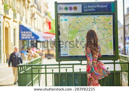 Young beautiful Parisian woman near the subway plan, looking for the direction - stock photo