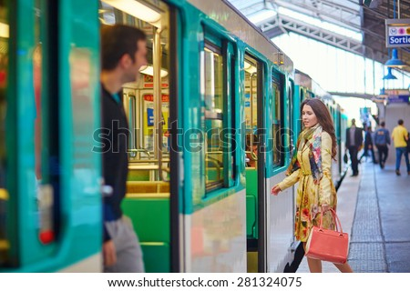 Young beautiful Parisian woman on a subway station, running to catch her train on the platform - stock photo