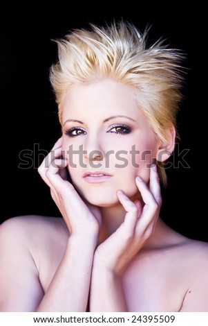 Young beautiful pensive blond isolated on black - stock photo