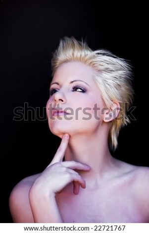 Young beautiful pensive blonde isolated on black - stock photo