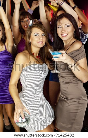 Young beautiful people dancing at disco with drinks. New Year - stock photo