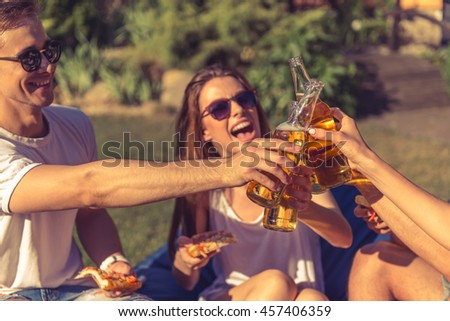 Young beautiful people in casual clothes and sun glasses are clinking bottles and laughing while resting outdoors - stock photo