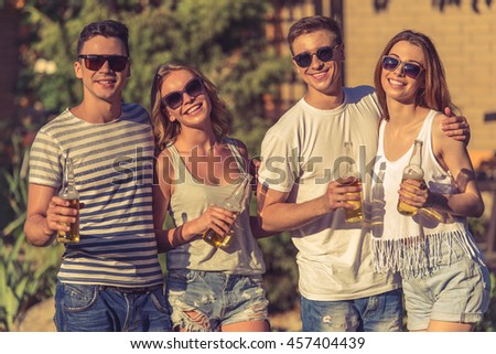 Young beautiful people in casual clothes and sun glasses are holding bottles of beverage, looking at camera and smiling while resting outdoors - stock photo