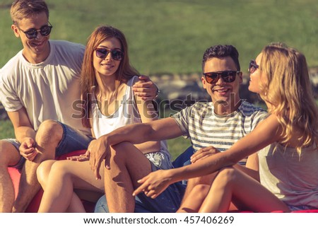 Young beautiful people in casual clothes and sun glasses are talking and smiling while resting outdoors - stock photo