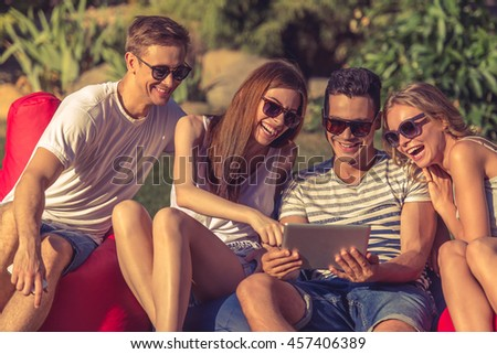 Young beautiful people in casual clothes and sun glasses are using a digital tablet, communicating and smiling, sitting on bean bag chairs while resting outdoors - stock photo
