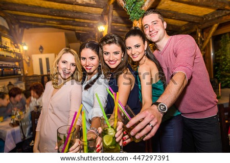 Young beautiful people with cocktails in bar or club - stock photo