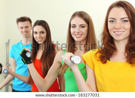 Young beautiful peoples engaged with dumbbells in gym