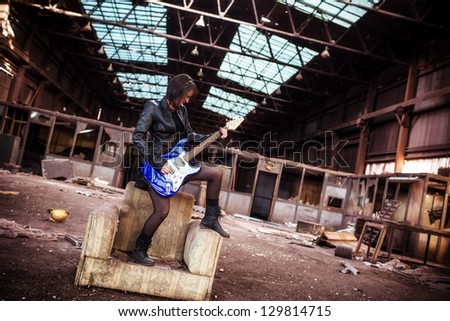 Young beautiful performer posing with her electric guitar. - stock photo
