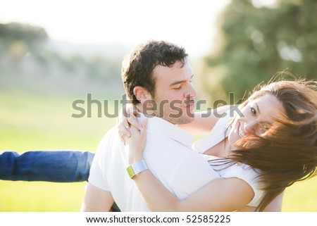 Young beautiful playful couple in action. Focus on him. - stock photo