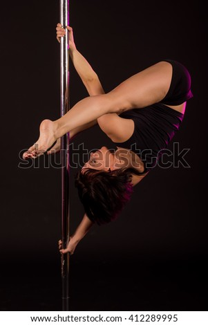 Young beautiful pole dancer on black background