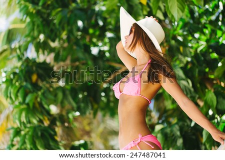 Young beautiful posing on the beach near the fence - stock photo