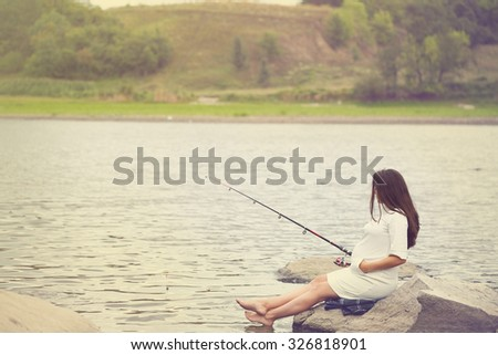 young beautiful pregnant woman fishing on the river bank