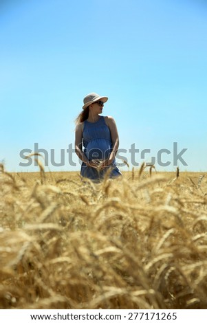 Young beautiful pregnant woman in the middle of wheat  field on a sunny summer day. Nature in the country. Blonde woman. - stock photo