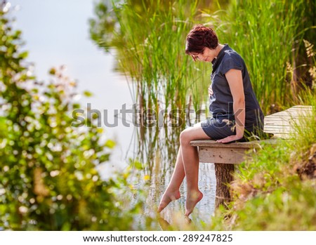 Young beautiful pregnant woman relaxing at the lake - stock photo