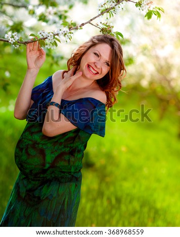 Young beautiful pregnant woman resting in spring garden