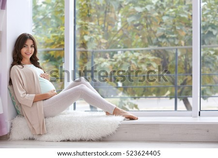 Young beautiful pregnant woman sitting on windowsill at home