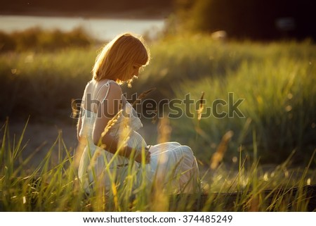 Young beautiful pregnant woman  walks on a meadow in Sunny summer day.
