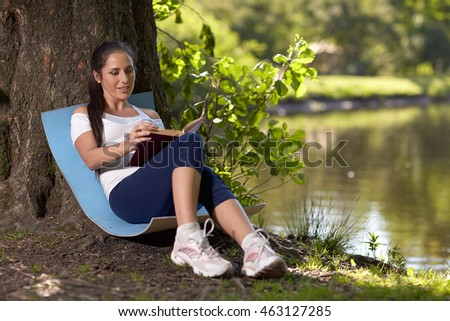 Young beautiful  pregnant  woman with book sits in the park.