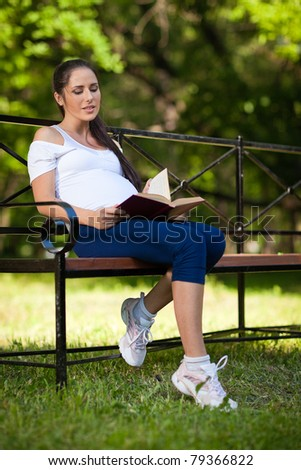 Young beautiful  pregnant  woman with book  sits on the bench in the park. - stock photo