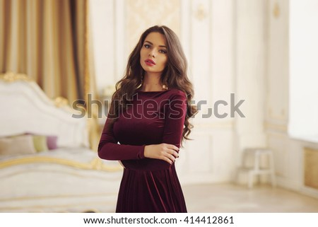 Young beautiful pretty elegant woman with long curly hair wearing cherry red evening dress and posing in bright interior