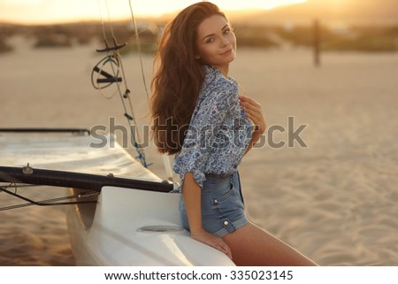 Young beautiful pretty girl sitting at sailing catamaran standing at sandy beach. Outdoor summer portrait with lovely soft evening sunset backlight - stock photo