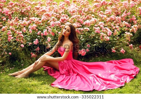 Young beautiful pretty girl with curly hair in pink silk dress sitting on grass near bushes of roses in blossom - stock photo