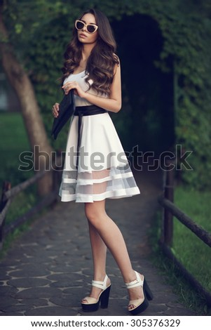 Young beautiful pretty stylish girl standing and posing at path in park. Woman in white dress with black belt, sunglasses and shoes. Fashion style toned portrait. - stock photo