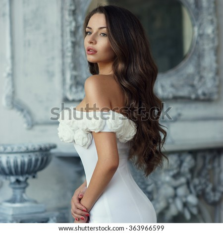 Young beautiful pretty woman in white evening dress standing near fireplace in luxury interior