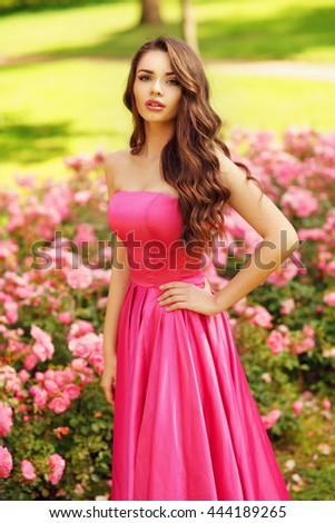 Young beautiful pretty woman posing in long evening luxury dress against bushes with pink roses on a sunny summer day. Vogue style fashion sensual portrait - stock photo