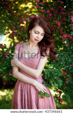Young beautiful pretty woman posing luxury dress against bushes with pink flowers on a sunny summer day. Vogue style fashion sensual portrait - stock photo
