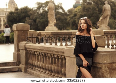 Young beautiful pretty woman walking at old city center and looking away. Stylish girl in black blouse and skirt posing outdoors                                - stock photo