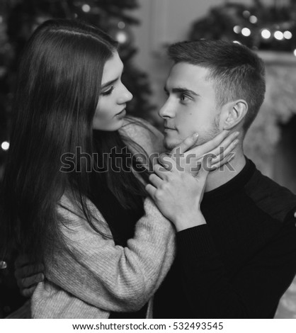 Young beautiful pretty woman with brown hair sitting at her husband or boyfriend knees and hugging him. Cute lovers staying at home and enjoying tome together