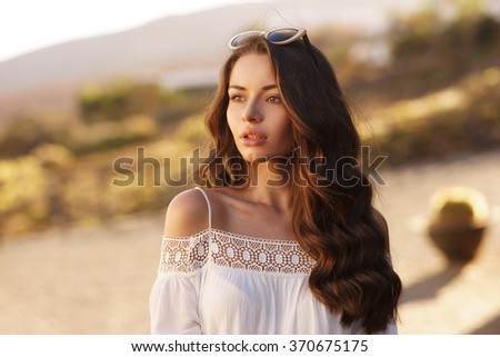 Young beautiful pretty woman with clean skin and long curly brunette hair looking away.
