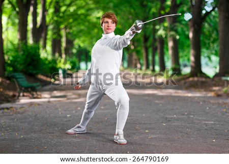 Young beautiful rapier fencer woman staying in park alley ready for competition - stock photo