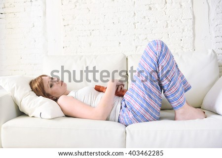 young beautiful red hair woman holding hot water bottle in a hurting tummy suffering stomach cramp and period pain lying on home couch in painful face expression female menstruation concept - stock photo