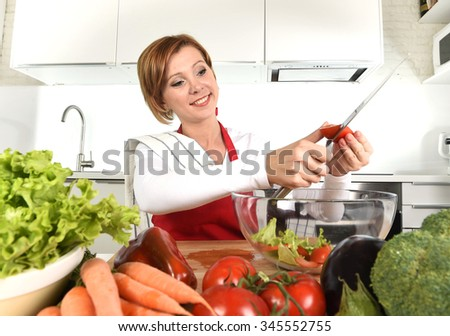 young beautiful red hair woman in red apron at home kitchen preparing vegetable salad with lettuce, carrots and slicing tomato smiling happy in healthy veggie eating and diet concept - stock photo