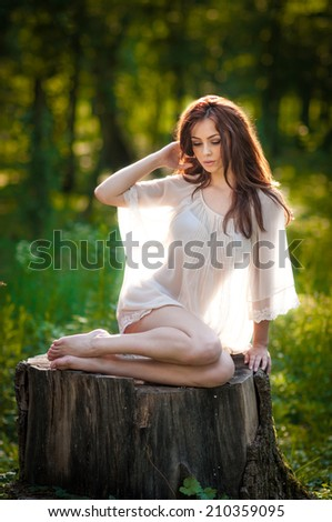 Young beautiful red hair woman wearing a transparent white blouse posing on a stump in a green forest. Fashionable sexy attractive girl sitting on hub in sunny day. Gorgeous redhead in garden. - stock photo