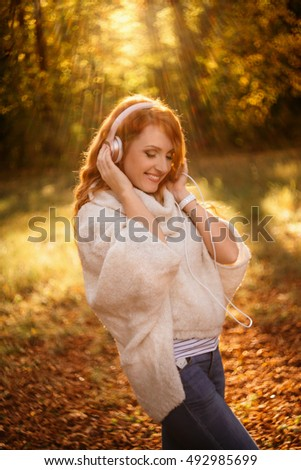 Young beautiful red-haired woman enjoying music with headphones in autumn park, sunny day